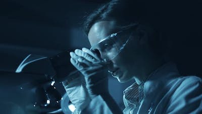 Woman Scientist is Looking Into Microscope Biochemical Research