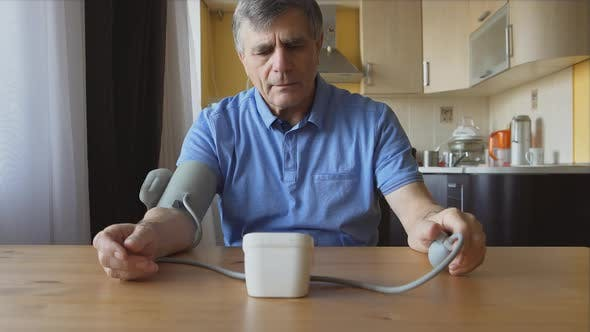 Thumbnail for An aged man measuring the blood pressure at home