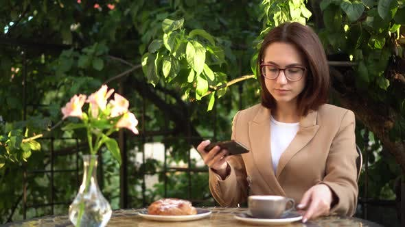 Thumbnail for A Young Business Woman Sits in a Cafe and Photographs Food on the Phone. Girl with Coffee and a Bun