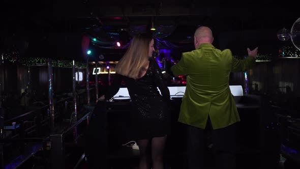 Back View of Female Caucasian DJ Mixing Music As Elderly Male Visitor Dancing Next To Controller