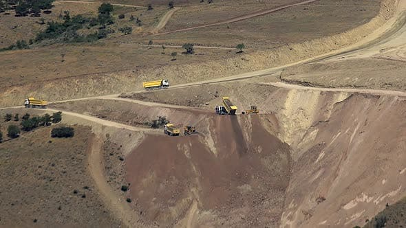 Thumbnail for Dump Trucks Discharge Soil Into The Valley
