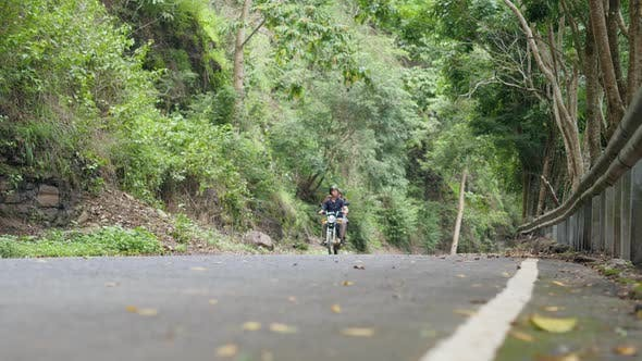 Thumbnail for Cinematic of Tourists Riding a Motorbike on Paved Road in Countryside of Asia.