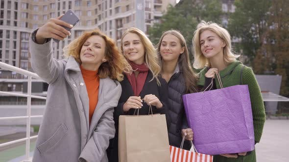 Thumbnail for Four Happy Friends with Shopping Bags and Taking Selfie. Four Fashion Women in the City. Leisure