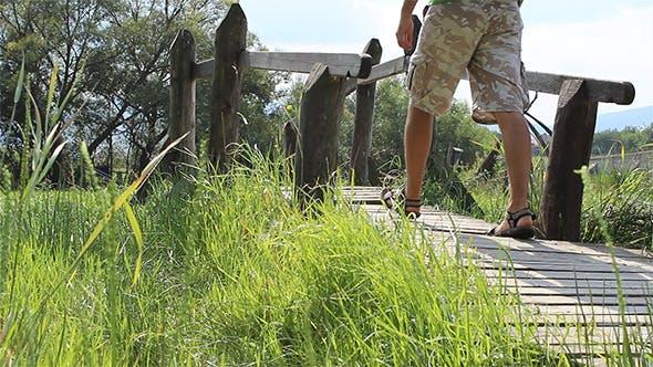 Thumbnail for Man Passing a Wooden Culvert