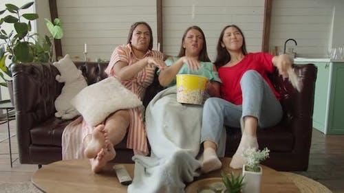 Mixed Race Women Expressing Dissatisfaction Watching TV Indoors