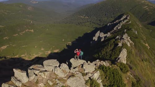 Aerial View of Hiker Couple of Tourists with Backpack on Top of a Mountain