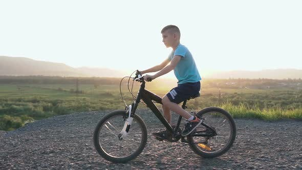 Cover Image for Beautiful Little Boy Who Rides a Black Bike in a Mountainous Place in the Summer