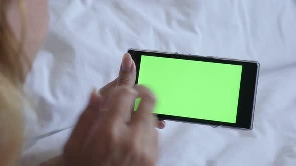 Thumbnail for Blonde weibliche Entspannung im Bett und Surfen auf greenscreen Handy-Display 4K 2160p 30fps UltraHD