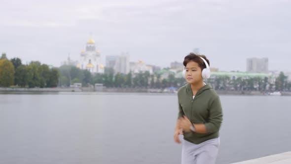 Thumbnail for Young Asian Boy in Headphones Running along Urban Riverside