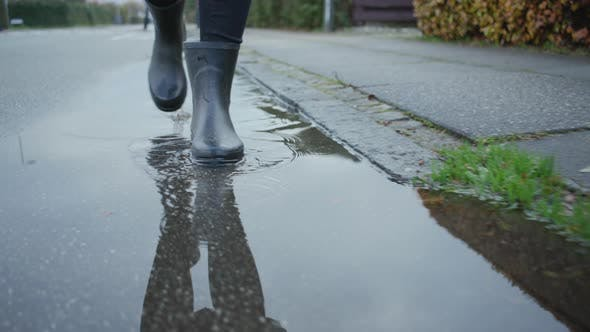 Thumbnail for Woman In Boots Walking Through Rain Puddle