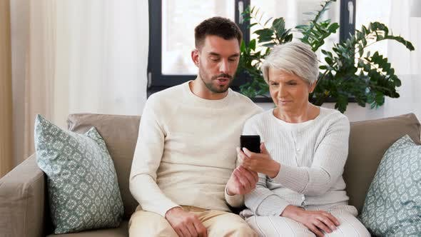 Cover Image for Old Mother and Adult Son with Smartphone at Home
