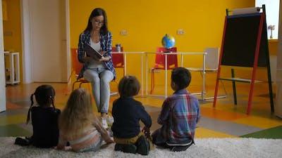 Beautiful Teacher Reading Fairy Tale To Pupils