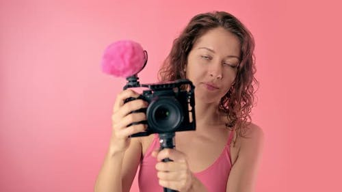 Portrait of a Young Beautiful Woman Using a Video Camera