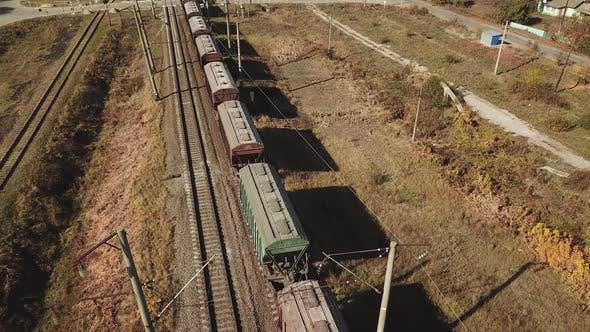 freight train is passing a highway. Aerial view of the freight train with wagons