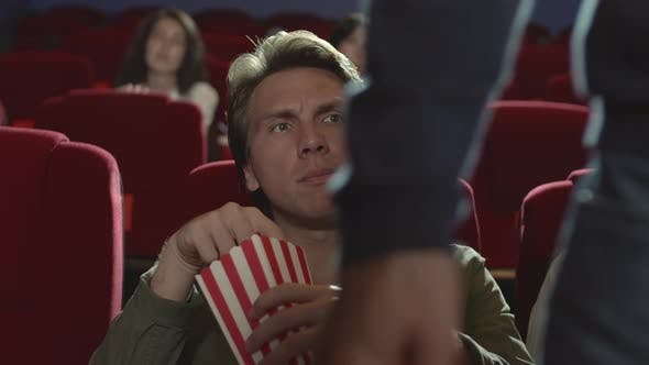 Thumbnail for Man Watching Film and Eating Popcorn in Cinema