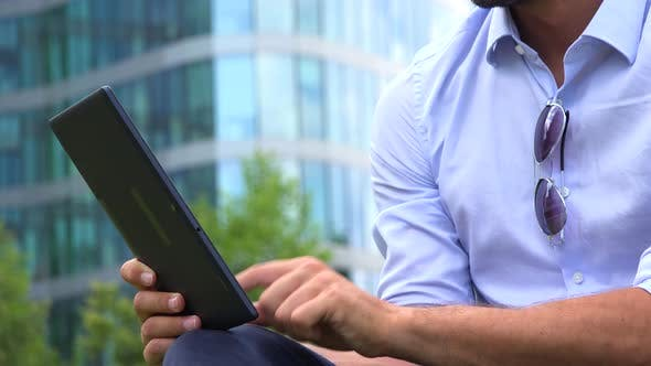 Thumbnail for A Young Handsome Businessman Works on a Tablet - Closeup - an Office Building in the Background