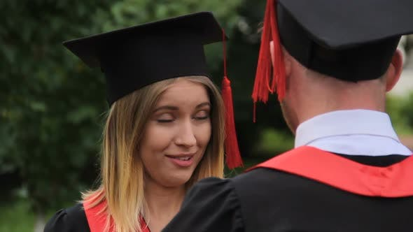 Thumbnail for Beautiful Woman in Academic Dress Talking to Graduating Boyfriend After Ceremony