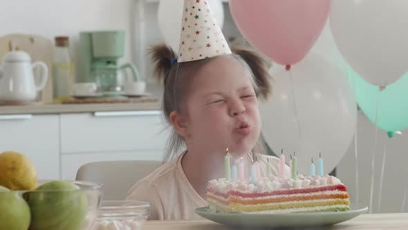 Birthday Girl with Down Syndrome Blowing out Candles