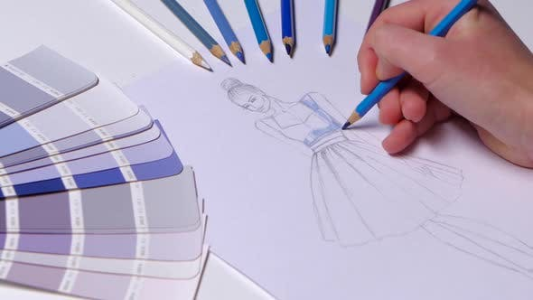 Thumbnail for Designer Dress Decorates a Sketch in Blue, on a Table Cloth Samples Lie. Close Up