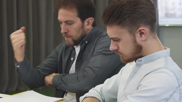 Thumbnail for Handsome Bearded Young Man Talking To His Mature Colleague at the Office