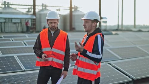 Technicians on Photovoltaic Farm of a Renewable Energy