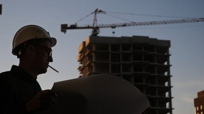 Silhouette builder engineer wear security helmet look at