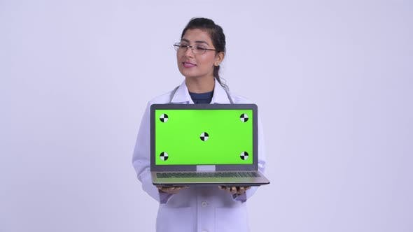 Thumbnail for Young Happy Persian Woman Doctor Thinking While Showing Laptop