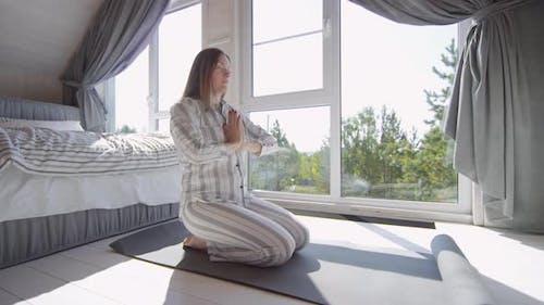 Woman Meditating in Bedroom in Morning