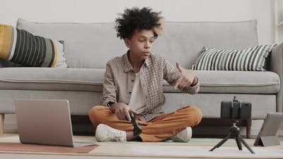 African Teenager Playing and Filming on Gadget