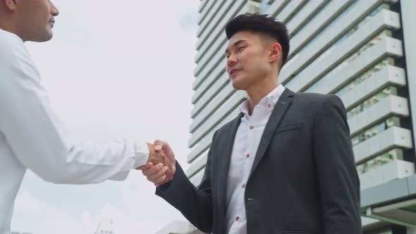 Asian businessmen making handshake greeting with co worker in the city building in background.