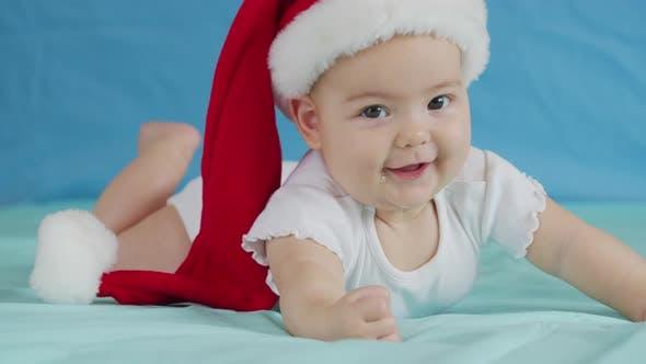 Thumbnail for Portrait of Adorable Infant Baby Girl Wearing Santa Hat. Christmas Celebration Concept.