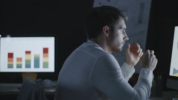 Thumbnail for Thoughtful Business Analyst Researching Graphs and Charts in Night Office