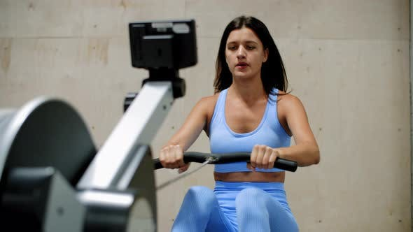 Thumbnail for Sporty Young Woman Training on Rowing Machine in Gym