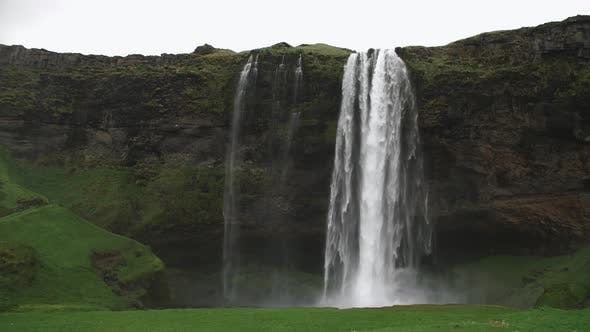 Cover Image for Waterfall With Lots Of Water And Flying White Birds And Tourists Walking Behind The Falls In Iceland