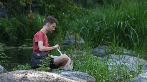 Thumbnail for Male Hiker Working on Laptop Pc in the Wild