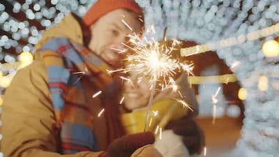 Couple Holding Christmas Sparkler and Kissing
