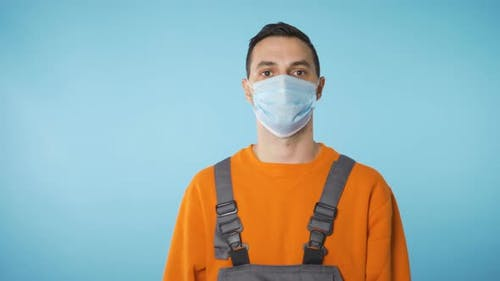 Builder Portrait with Face Mask Covid 19 Restrictions in Blue Background
