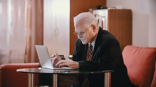 Thumbnail for Elderly Grandfather - Old Grandfather with Glasses and a Jacket Is Typing on a Computer