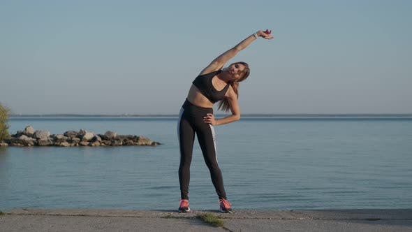 Thumbnail for Athletic Girl Is Warming Up Before a Jogging Evening on the Seashore
