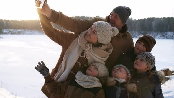 Thumbnail for Family Taking Selfies in Winter Woodland