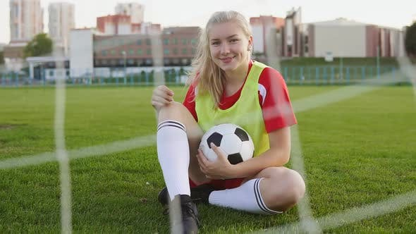 Portrait of a smiling girl football player sitting on field with soccer ball