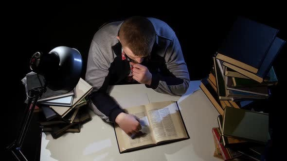 Thumbnail for Man Leafing Through the Book and Falls Asleep. Black Background. View From Above
