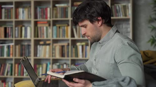 Portrait of a Man Sitting on a Sofa with a Laptop on the Background of a Bookshelf