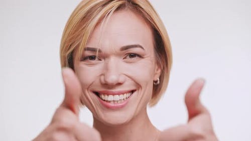 Blonde Caucasian Middleaged Female Smiling at Camera Winking Eye Showing Ok and Touching Hair on