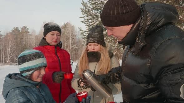Thumbnail for Vater Gießen Heißer Tee aus Thermoskanne für Familie bei Winterspaziergang im Wald