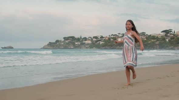 Cheerful Girl Dancing at Coastline