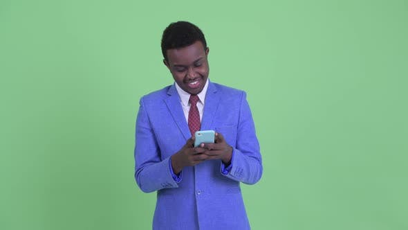 Thumbnail for Happy Young African Businessman Thinking While Using Phone