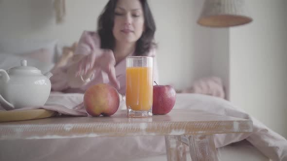 Blurred Caucasian Woman Taking Fresh Apple From Table and Crawling Away on Bed at Home. Happy