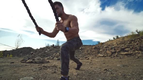 Professional sportsman working out with battle ropes