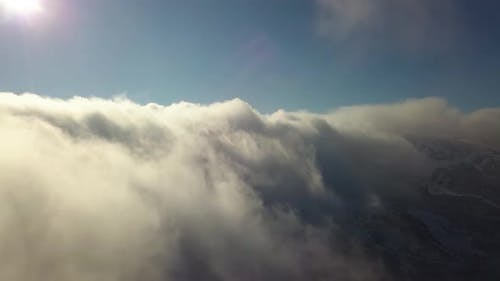 Aerial view from above of white puffy clouds covering snowy mountain tops in bright sunny day.